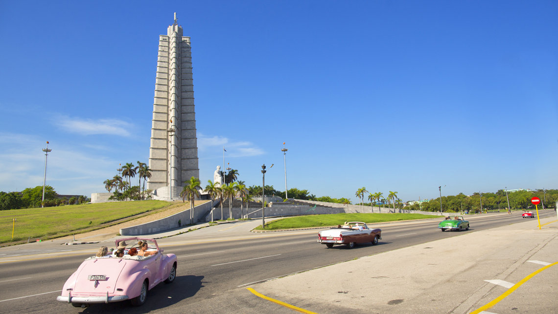 Classic American cars drive through Revolution Square in Havana